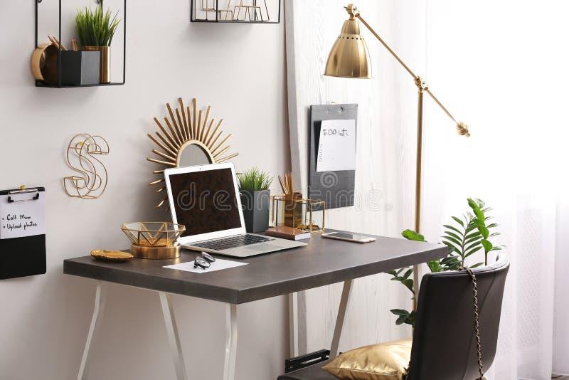 Moderne werkplaats met laptop en gouden decor op bureau Modieus binnenlands ontwerp stock afbeelding