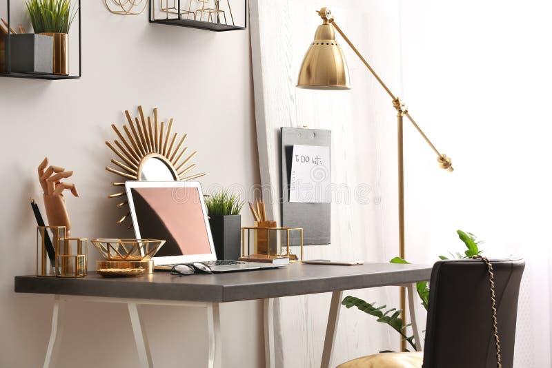 Moderne werkplaats met laptop en gouden decor op bureau Modieus binnenlands ontwerp stock foto's