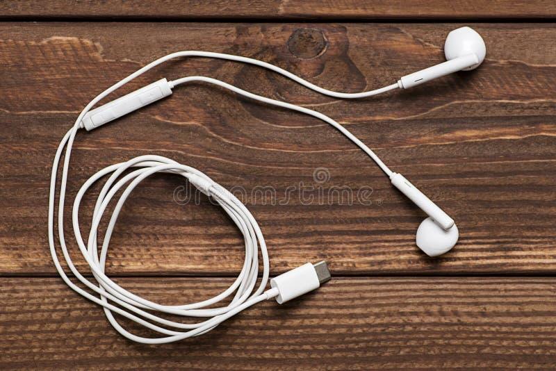Moderne witte oortelefoon, wit in oorhoofdtelefoon op houten lijst Witte oortelefoons over houten raad royalty-vrije stock afbeelding
