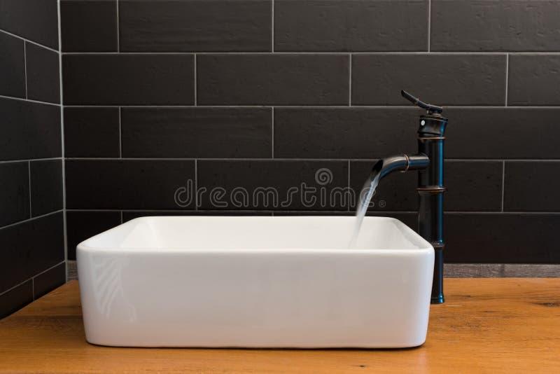 Moderne witte vierkante gootsteen in badkamers met zwarte tegels en zwarte tapkraan in vorm van bamboe Modern badkamersontwerp royalty-vrije stock afbeeldingen