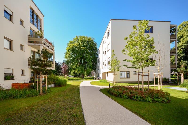 Moderne Wohngebäude in einer grünen Umwelt, nachhaltige Stadtplanung lizenzfreie stockbilder