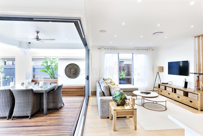 Moderne woonkamer in bijlage aan het terras en het dineren gebied stock fotografie