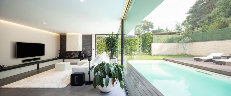 Moderne woonkamer die de tuin en het zwembad overzien stock foto's