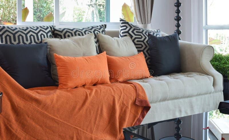 Moderne woonkamer met bruine en oranje bank en hoofdkussens royalty-vrije stock afbeeldingen