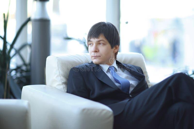 Moderne zakenmanzitting als voorzitter in de hal van het moderne bureau stock foto's