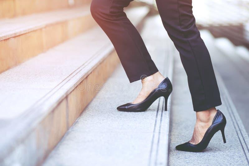 Moderne zakenvrouw die werkt, sluit zijn benen op de trap op in de moderne stad, in het spitsuur om in dienst te werken, en schie stock fotografie