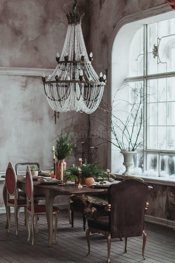 Moderne zoldereetkamer met hoog plafond, uitstekende leunstoelen, lege grijze concrete muur, houten vloer, eettafel met stock foto