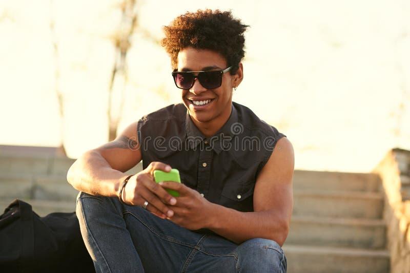Moderne zwarte jonge mens die terwijl het typen van een bericht glimlachen stock afbeeldingen