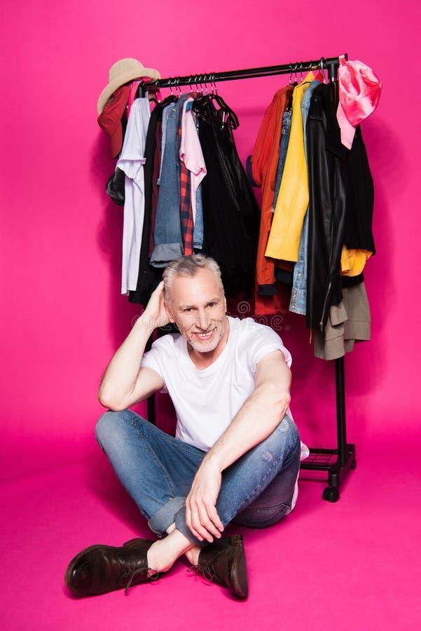 Moderner älterer Mann, der unter Kleidung auf Aufhängern sitzt lizenzfreie stockbilder
