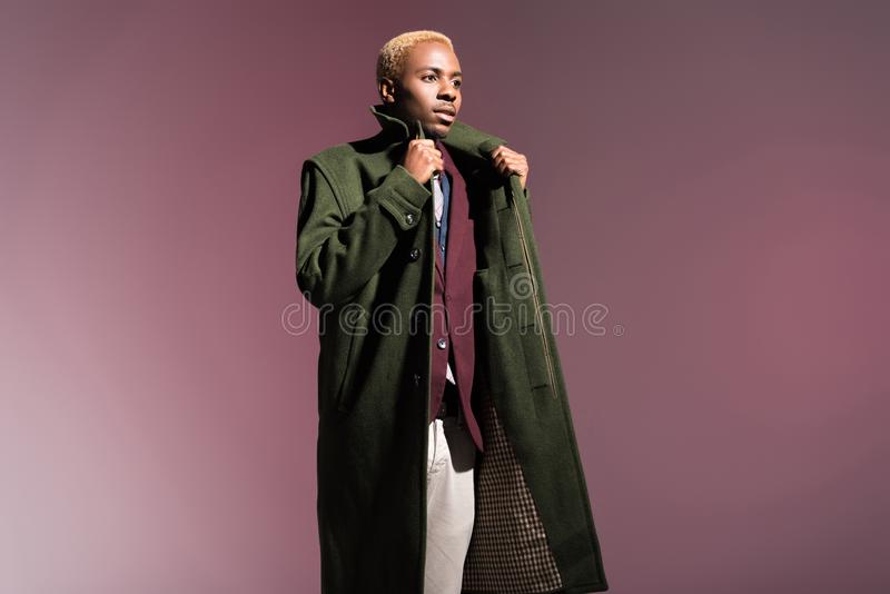Moderner afrikanischer Mann im Mantel, der weg schaut stockbilder