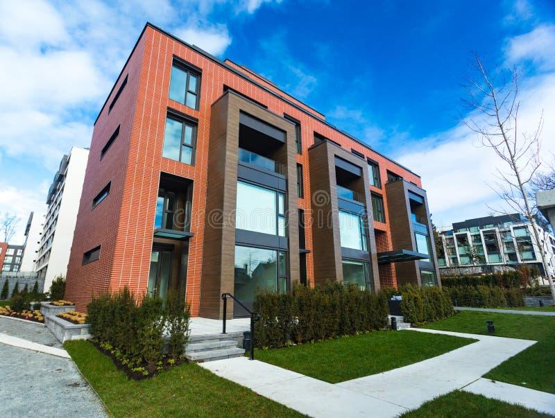 Moderner Appartementkomplex des roten Backsteins mit Felsenzaunwand Hauptkomplexe Immobilien der wohngebäude lizenzfreies stockfoto