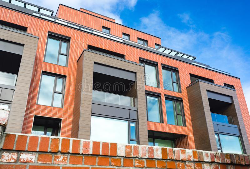 Moderner Appartementkomplex des roten Backsteins mit Felsenzaunwand Hauptkomplexe Immobilien der wohngebäude lizenzfreie stockfotografie