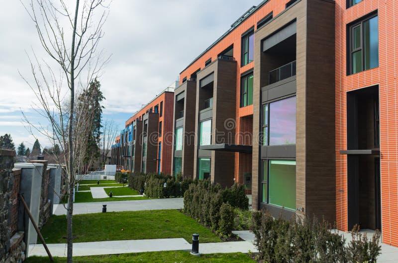 Moderner Appartementkomplex des roten Backsteins mit Felsenzaunwand Hauptkomplexe Immobilien der wohngebäude lizenzfreie stockfotos