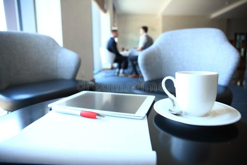 Moderner Arbeitsplatz mit digitalem Tablet-Computer und Handy, Tasse Tee, Stift und Papier mit Zahlen lizenzfreies stockbild