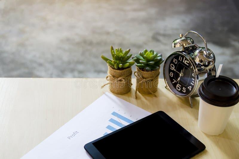 Moderner Arbeitsplatz mit digitaler Tablette, Naturkaktusbaum, Handy, Uhr, Tasse Kaffee und Papieren mit Gewinnzahlen lizenzfreies stockbild