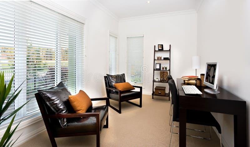 Moderner Arbeitszimmerinnenraum verzierte unter Verwendung dunkle Farbmöbel a lizenzfreie stockfotografie