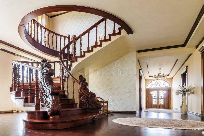 Moderner Architekturinnenraum mit klassischer eleganter Luxushalle mit gebogener glatter hölzerner Bügeltreppe im modernen Gescho stockbild
