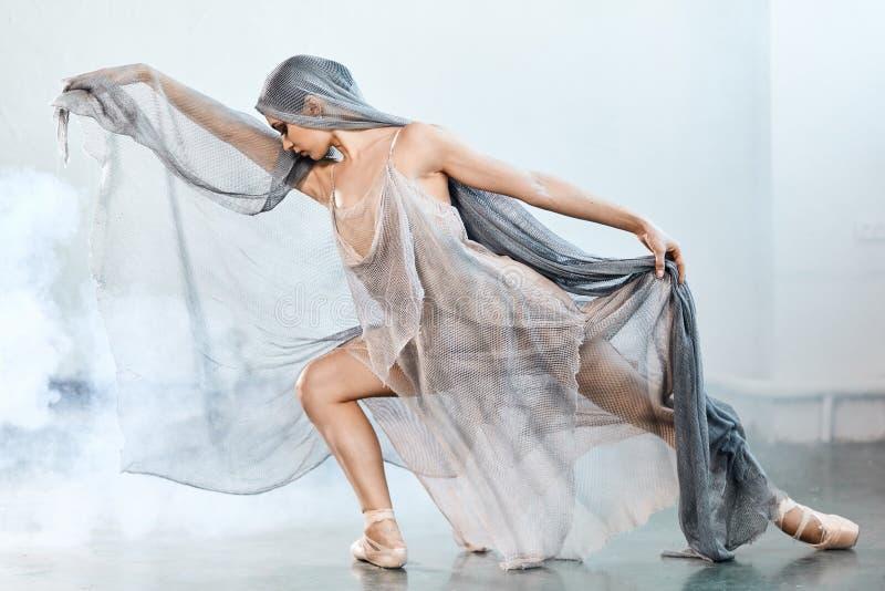 Moderner Artballettt?nzer ex auf einem grauen Hintergrund des Studios im Nebel stockfotografie