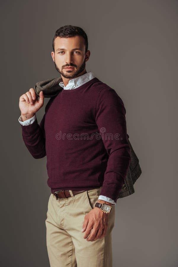 moderner bärtiger Mann, der in Burgunder-Strickjacke mit Herbstjacke auf Schulter aufwirft lizenzfreie stockbilder