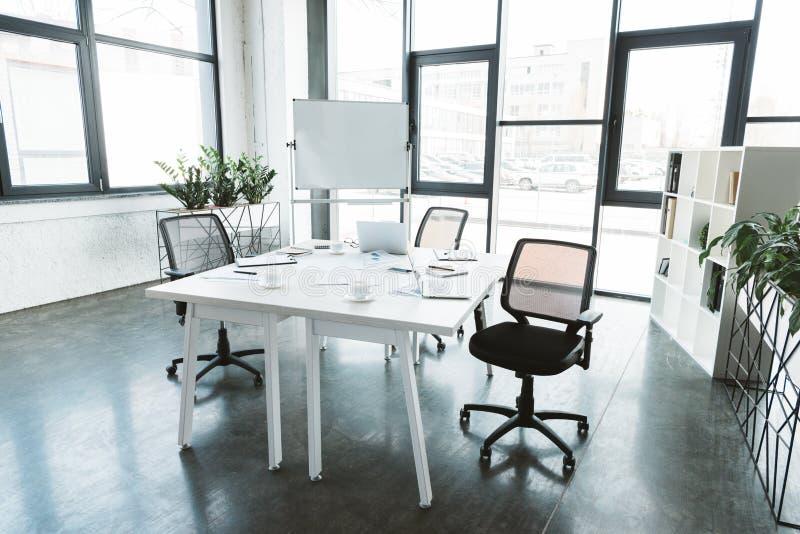 moderner Büroinnenraum mit Schreibtisch, Papiere, Stühle stockbild