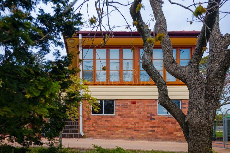 Moderner Backsteinbau mit den hölzernen Fenstern gesehen durch Bäume stockbild