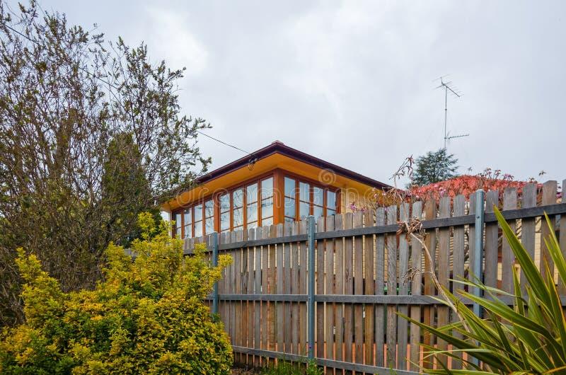 Moderner Backsteinbau mit den hölzernen Fenstern umgeben durch Zaun stockfoto