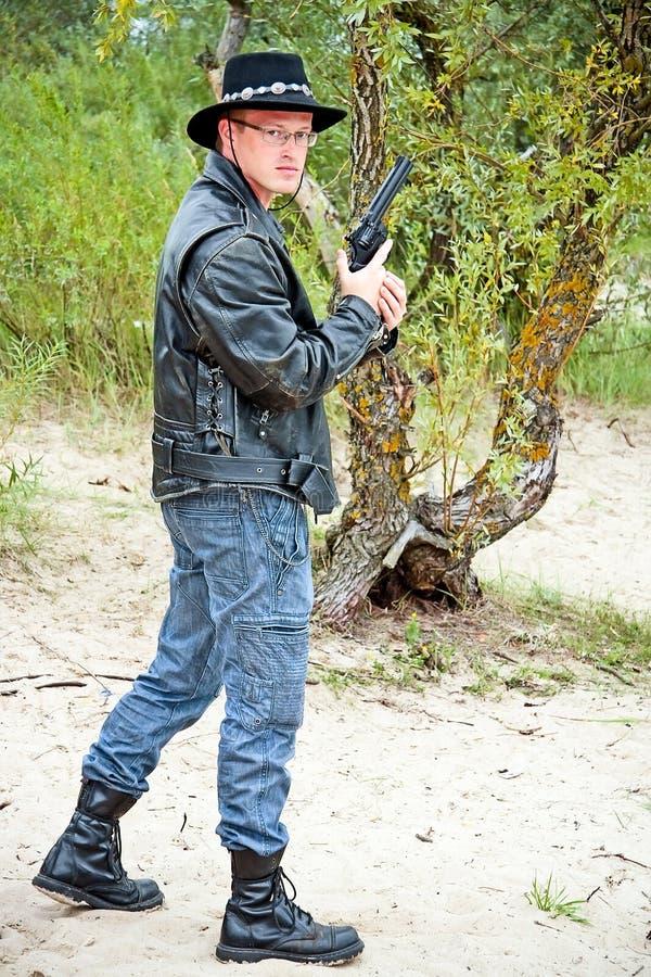 Moderner Cowboy mit dem Revolver, der auf Sand steht stockbild