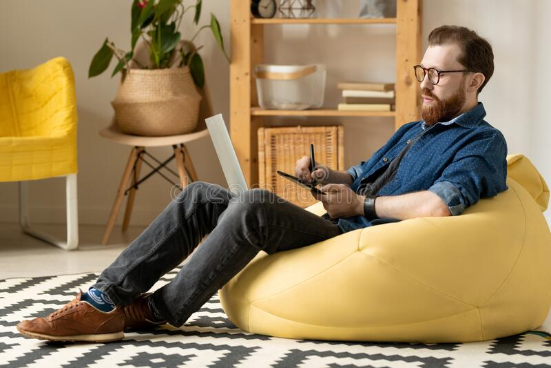 Moderner Designer sitzt in Bohnentaschen lizenzfreie stockfotografie