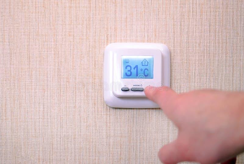 Moderner digitaler programmierbarer Thermostat mit Flüssigkristallanzeige und -knöpfen, mit weißer Platte auf einem weißen Hinter stockfotografie