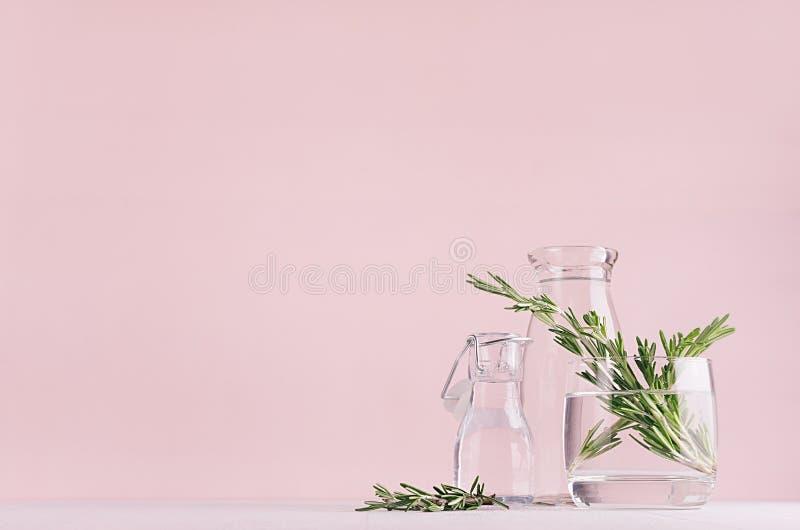 Moderner einfacher Kunstrosaausgangsdekor mit Grünpflanze in den transparenten Vasen auf weißer hölzerner Tabelle des weichen Lic stockbilder