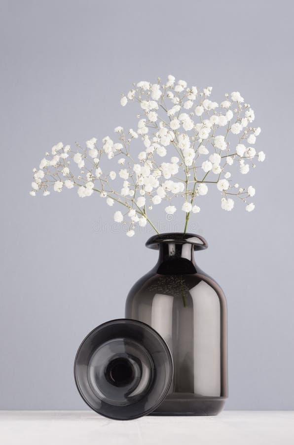 Moderner eleganter Hauptdekor des schwarzen transparenten glatten Glasvase mit kleinen Blumen, Dekorationsbereich auf grauer Farb lizenzfreies stockbild