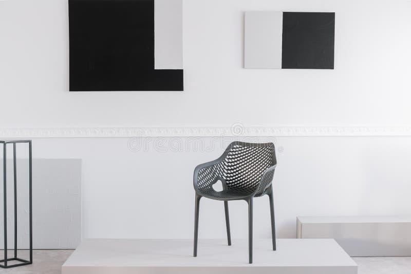 Moderner grauer Metallstuhl auf weißer Plattform im fantastischen Ausstellungsraum stockfotos