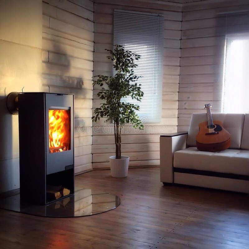 Moderner hölzerner brennender Ofen innerhalb des gemütlichen Wohnzimmers stockfoto