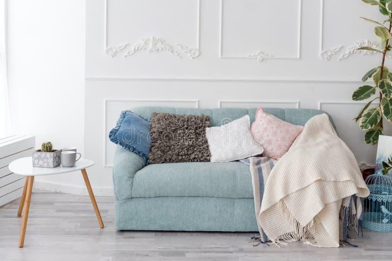 Moderner hölzerner Couchtisch und gemütliches Sofa mit Kissen Wohnzimmerinnen- und einfaches modernes Hauptdekorkonzept lizenzfreies stockfoto