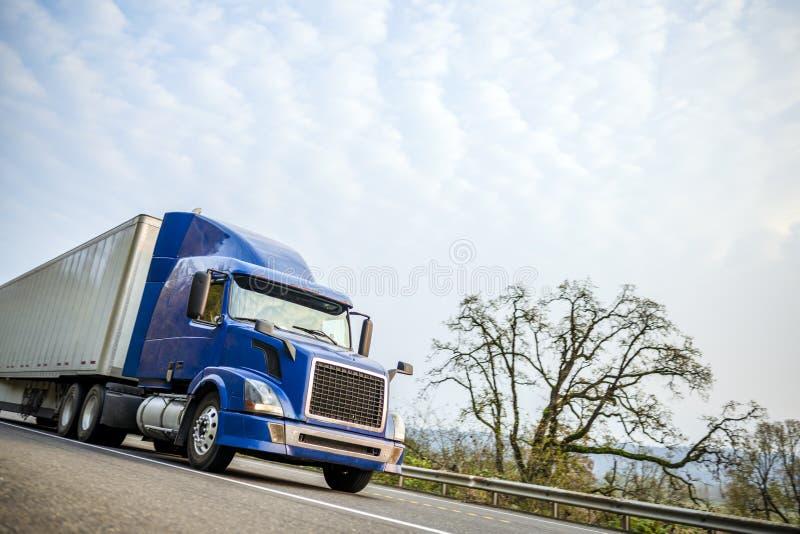 Moderner halb LKW des gro?en Anlagenblaus mit dem trockenen des Packwagens Anh?nger halb, der auf die Stra?e mit Sicherheitszaun  lizenzfreies stockbild