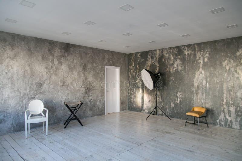 Moderner heller Dachboden-ähnlicher Raum mit Designerstühlen und -beleuchtung Graue Wände mit der Beschaffenheit des Betons hölze lizenzfreie stockbilder