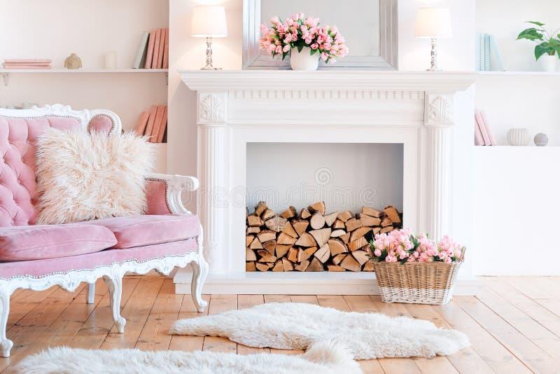 Moderner heller Innenraum mit Kamin, Frühlingsblumen und gemütlichem rosa Sofa stockfotografie