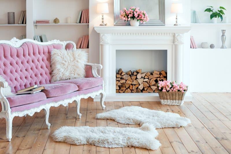 Moderner heller Innenraum mit Kamin, Fr?hlingsblumen und gem?tlichem rosa Sofa lizenzfreies stockfoto
