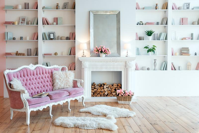 Moderner heller Innenraum mit Kamin, Fr?hlingsblumen und gem?tlichem rosa Sofa stockfotografie