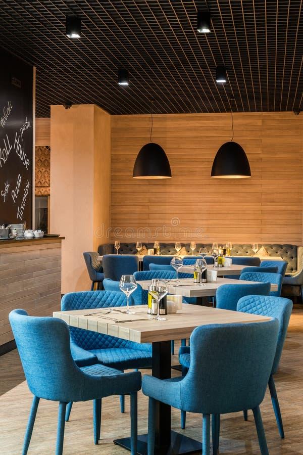 Moderner Innenraum der angenehmen Art des Restaurants europäischen mit blauen Stühlen und Weingläsern auf Tabellen, vertikaler Sc stockfotos