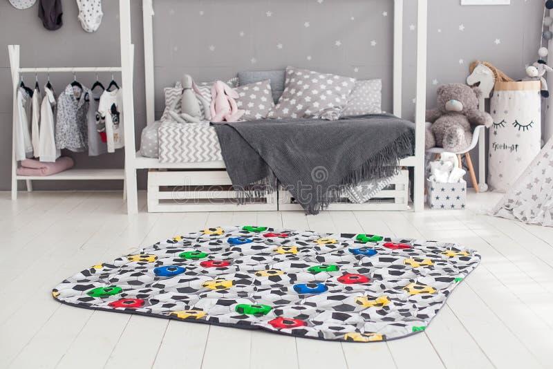 Moderner Innenraum des Kind-` s Schlafzimmers mit Teppich in der Front lizenzfreie stockbilder