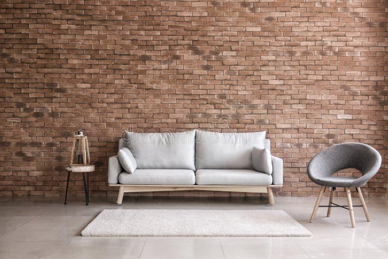 Moderner Innenraum des Wohnzimmers mit bequemem Sofa und Lehnsessel nahe Backsteinmauer stockbilder