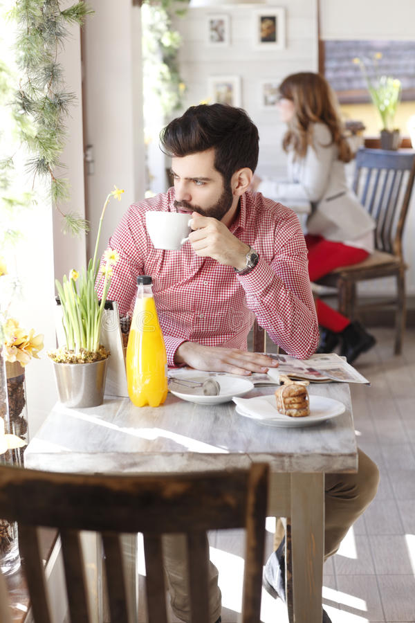 Moderner junger Mann, der in der Kaffeestube sitzt stockbilder