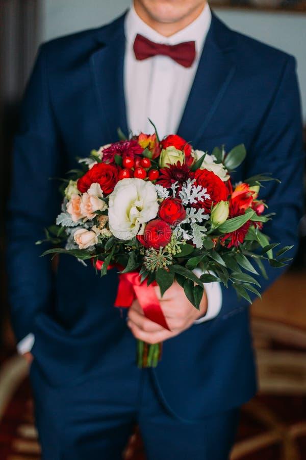 Moderner junger Mann, der Hochzeitsblumenstrauß von roten und weißen Blumen hält lizenzfreie stockfotos