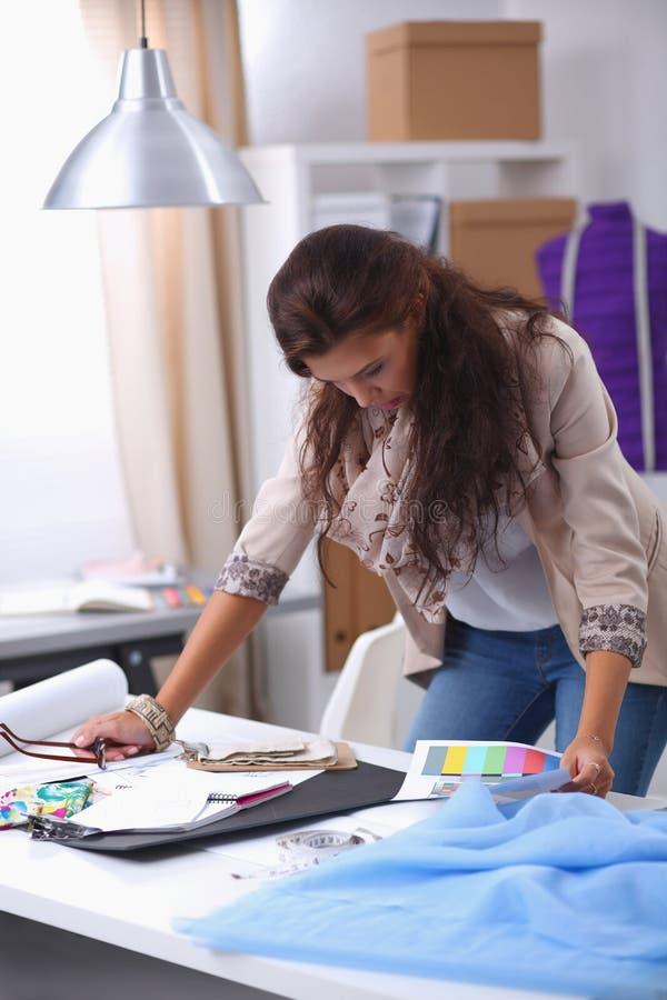 Moderner junger Modedesigner, der am Studio arbeitet stockfotografie