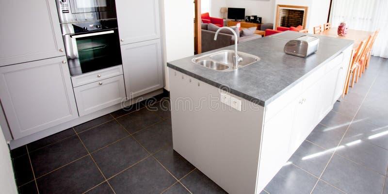 Moderner Kücheninnenraum mit Insel, Wanne und Kabinetten im neuen Luxushaus lizenzfreie stockbilder