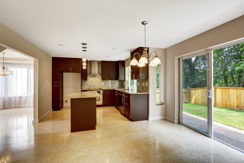Moderner Küchenraum mit braunen Mattkabinetten und Ausgang zum backya lizenzfreie stockbilder