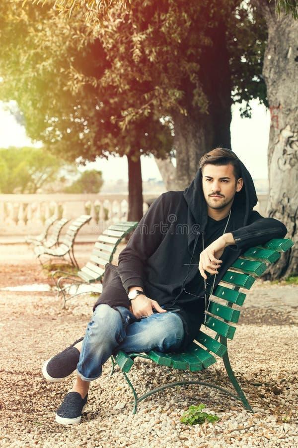 Moderner kühler junger Mann, der auf einer Bank in einem Park mit Bäumen sich entspannt stockbild