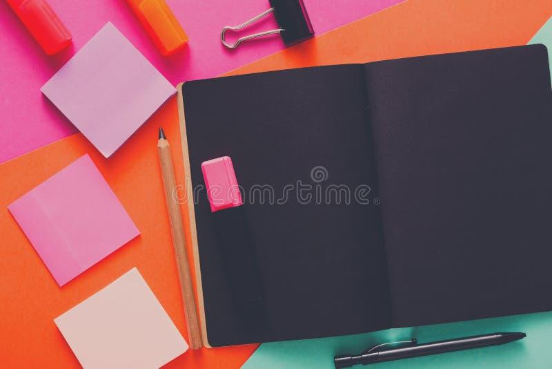 Moderner kreativer Arbeitsplatz mit stilvollem schwarzem Notizblock lizenzfreie stockfotografie