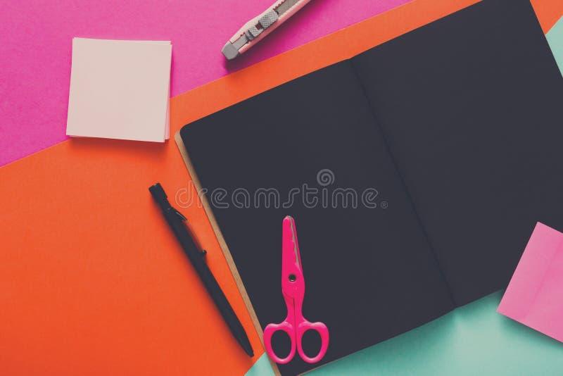 Moderner kreativer Arbeitsplatz mit stilvollem schwarzem Notizblock stockbild